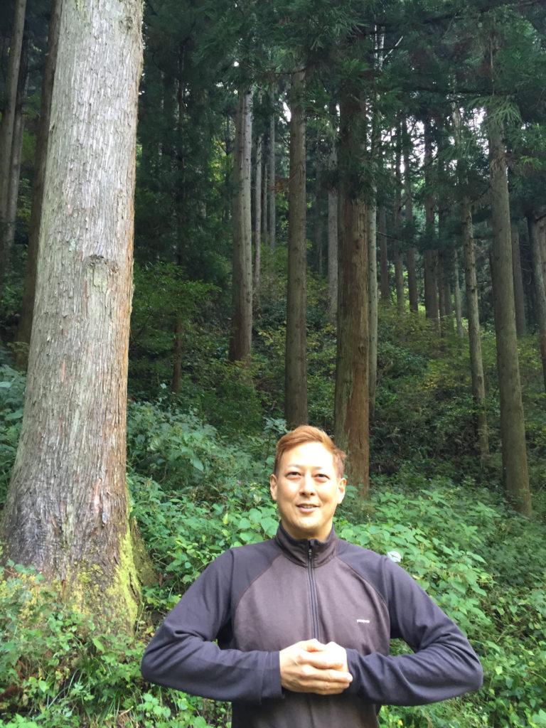 お寺の近くの森の前で。