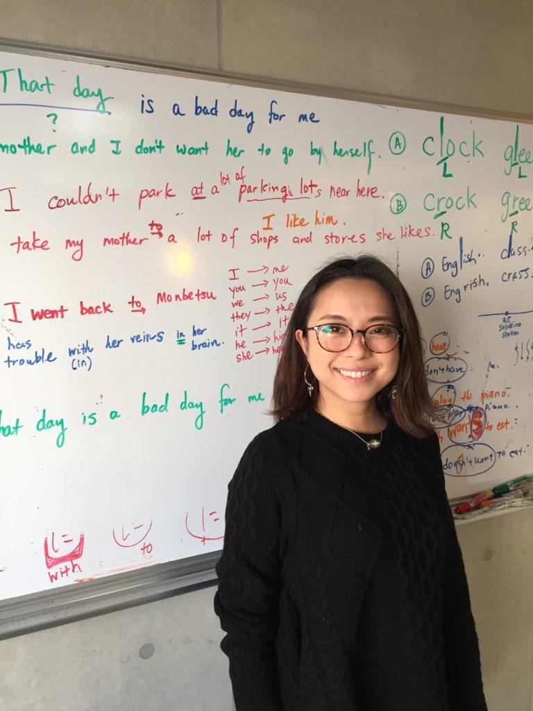 英会話授業のホワイトボードの前に立つ生徒さん。
